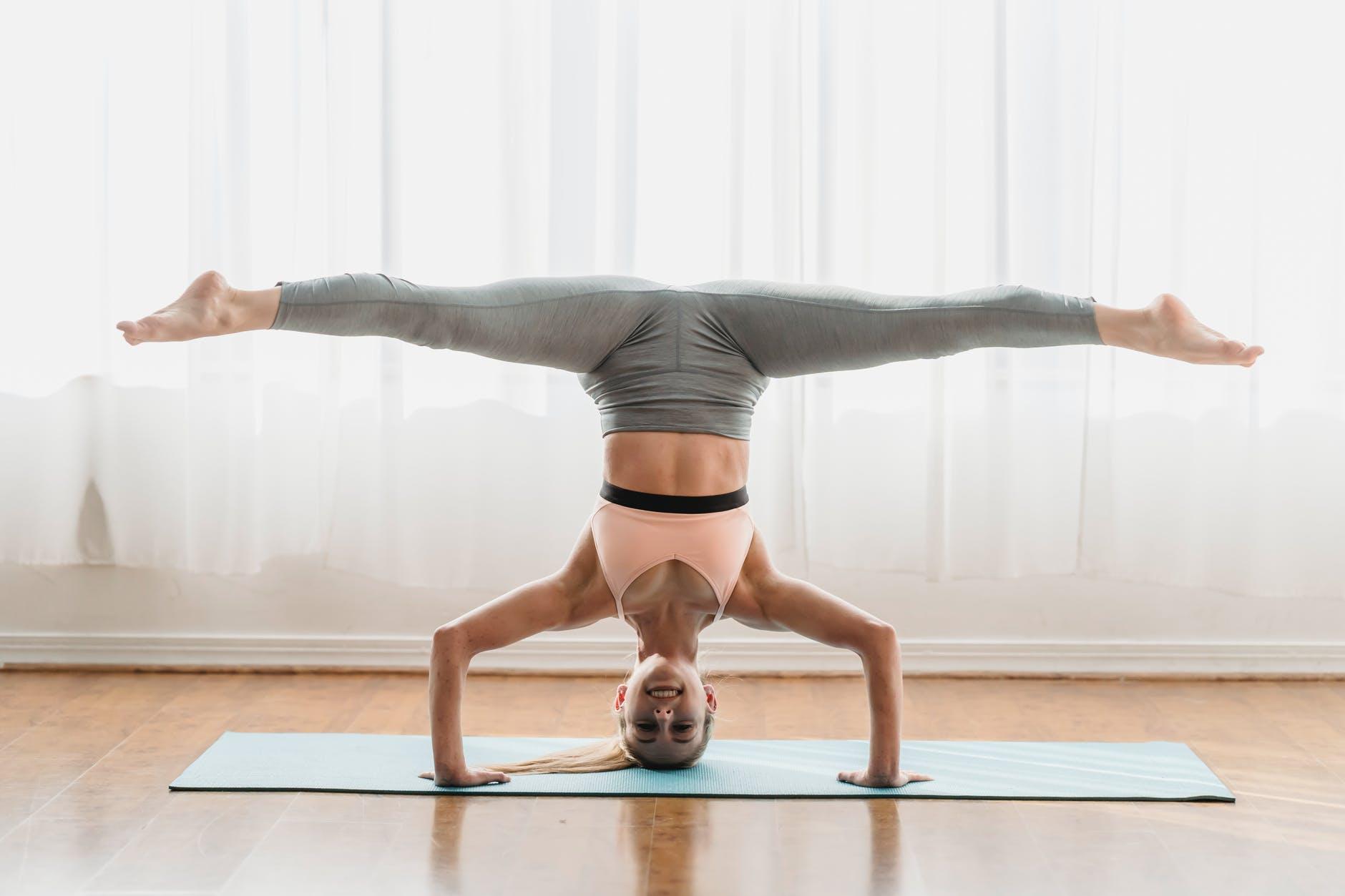 sportive woman doing headstand split